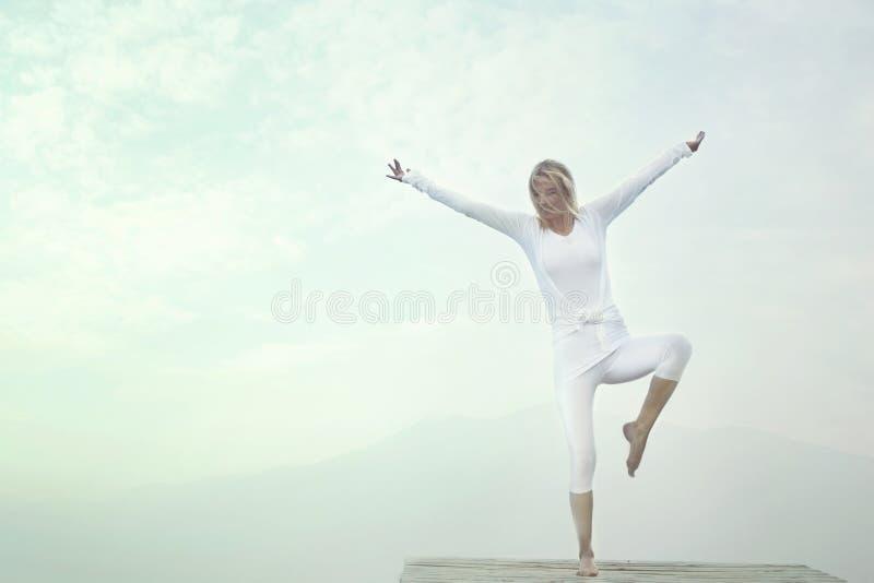 做瑜伽的妇女在蓝天前面行使 免版税库存图片