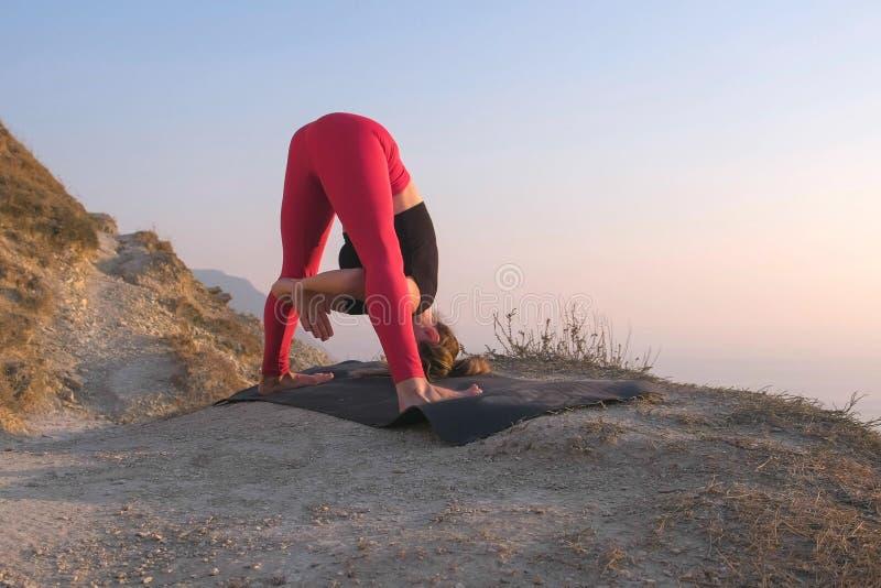 做瑜伽的妇女美丽的景色舒展在山有海视图在日落 回到视图 免版税库存图片
