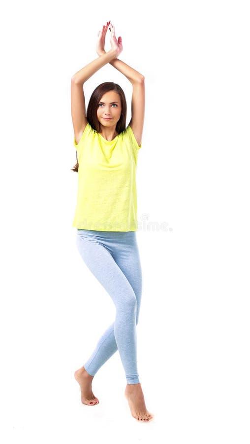 做瑜伽的妇女,被隔绝反对白色背景 免版税库存照片