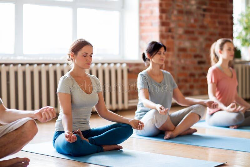 做瑜伽的小组妇女在演播室行使 免版税库存图片