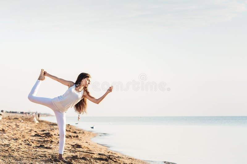 做瑜伽的少女在海灘的日出 免版稅庫存圖片圖片