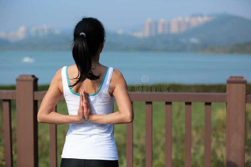 做瑜伽的少妇在城市公园行使 免版税库存图片