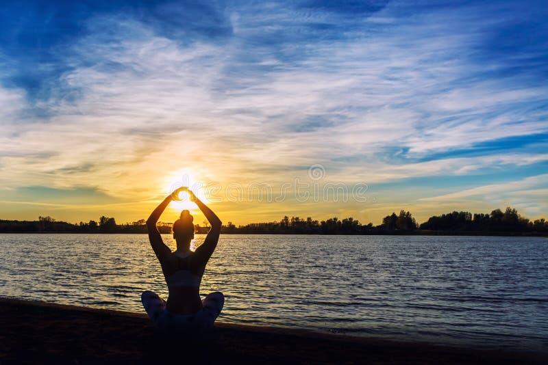 做瑜伽的少妇在湖海滩行使在日落. 火箭筒, 反映.图片