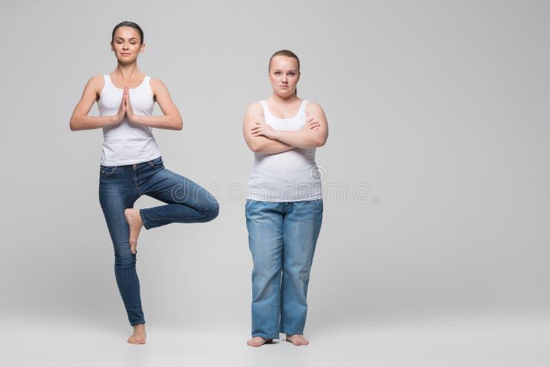做瑜伽的平静的亭亭玉立的女孩在肥胖夫人附近 免版税库存照片