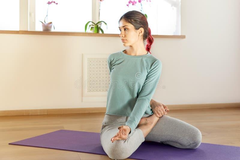 做瑜伽的年轻可爱的体育女孩妇女行使坐的o 免版税图库摄影