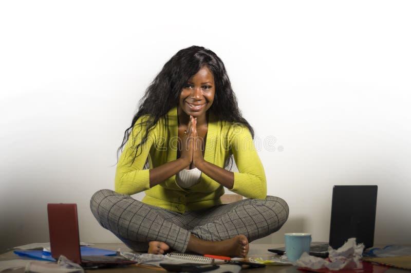 做瑜伽的年轻愉快和可爱的非裔美国人的女商人坐在办公室杂乱书桌文书工作微笑充分放松 免版税库存图片