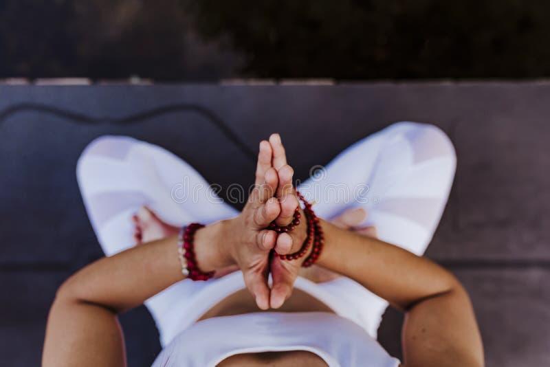 做瑜伽的接近的观点的无法认出的年轻亚裔妇女在公园 坐有祈祷的手位置的桥梁和 免版税库存照片