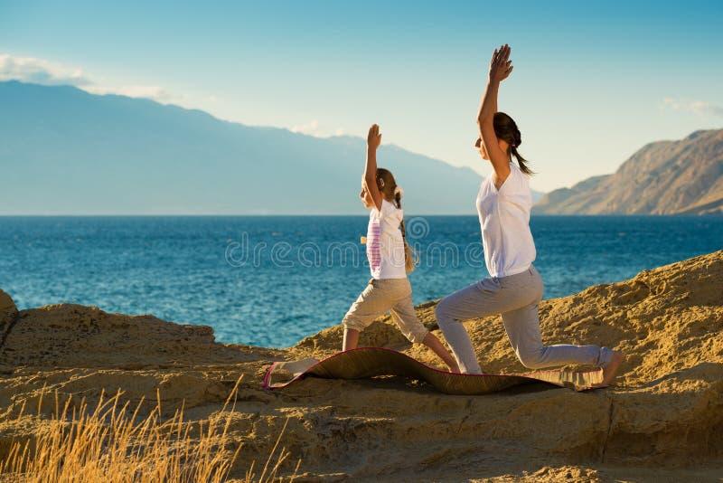 做瑜伽的母親和女兒在海灘行使. 天空, 安靜.圖片