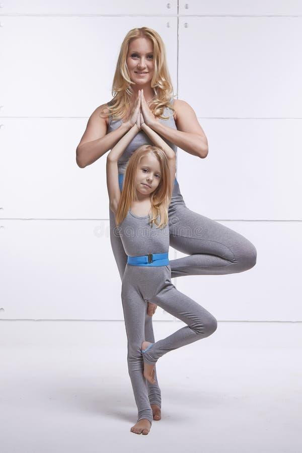 做瑜伽的母亲和女儿行使,健身,佩带同样舒适的田径服,家庭体育,体育的健身房被配对的holdin 免版税库存照片