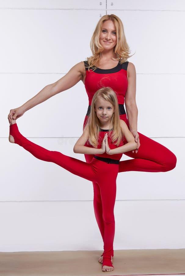 做瑜伽的母亲和女儿行使,健身,健身房体育pai 库存照片