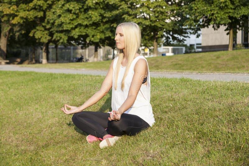 做瑜伽的白肤金发的妇女 库存照片
