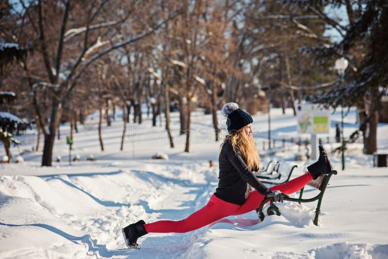 做瑜伽的美丽的妇女户外在雪 免版税库存照片