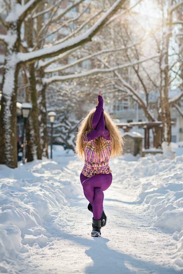 做瑜伽的美丽的妇女户外在雪 库存照片