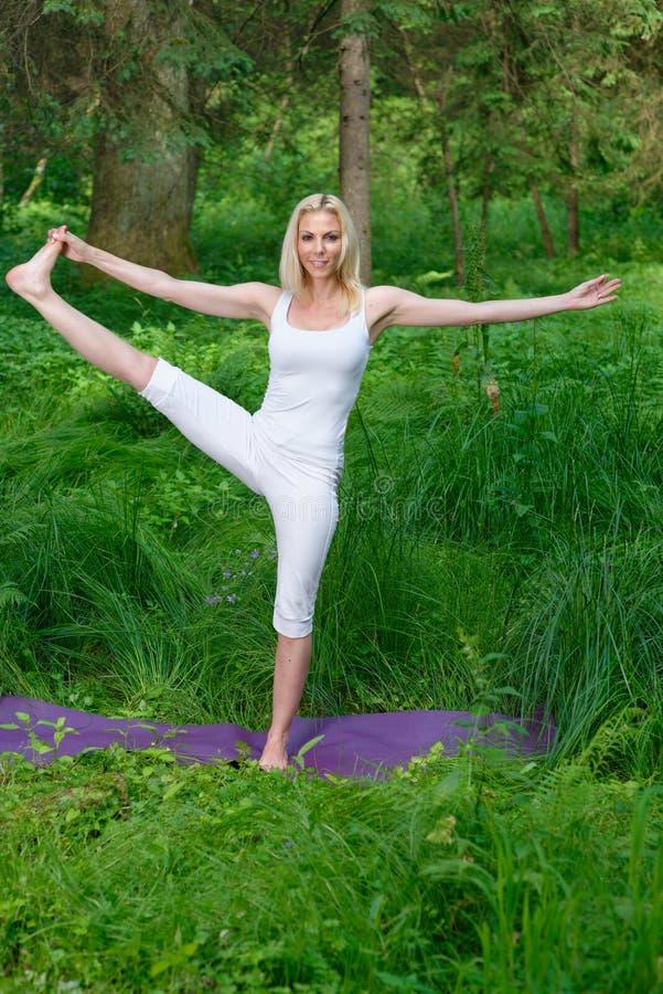 做瑜伽的美丽的少妇外面 库存图片