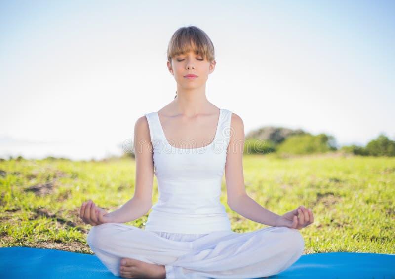 做瑜伽的美满的自然少妇 免版税库存图片