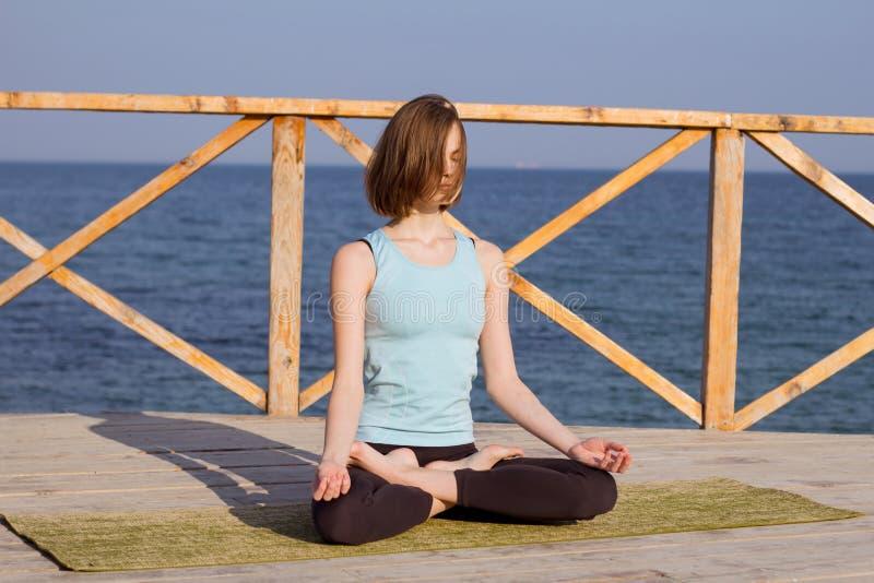 做瑜伽的年轻亭亭玉立的妇女行使夏天海背景 库存图片