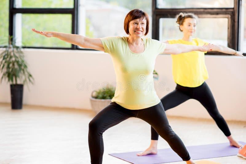 做瑜伽的年轻和老妇人 免版税库存图片
