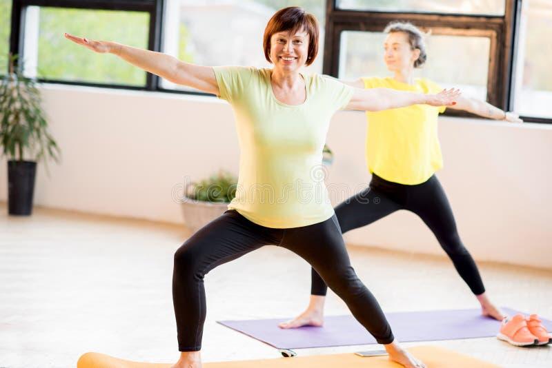 做瑜伽的年轻和老妇人 库存图片