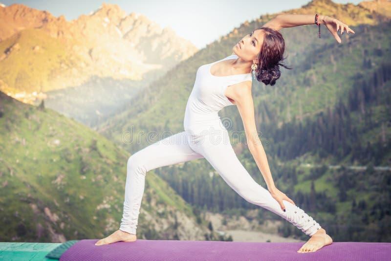 做瑜伽的锻炼被启发的亚裔妇女在山脉 库存照片
