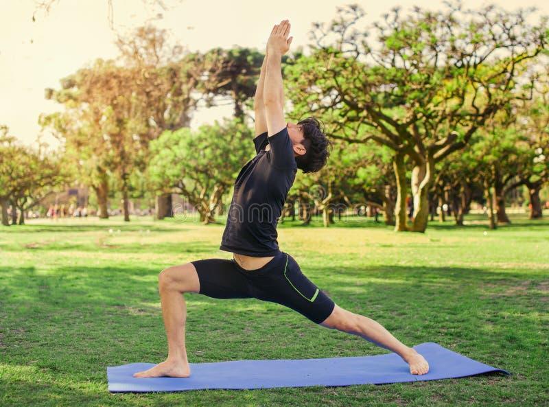 做瑜伽的年轻英俊的人在公园 免版税库存图片