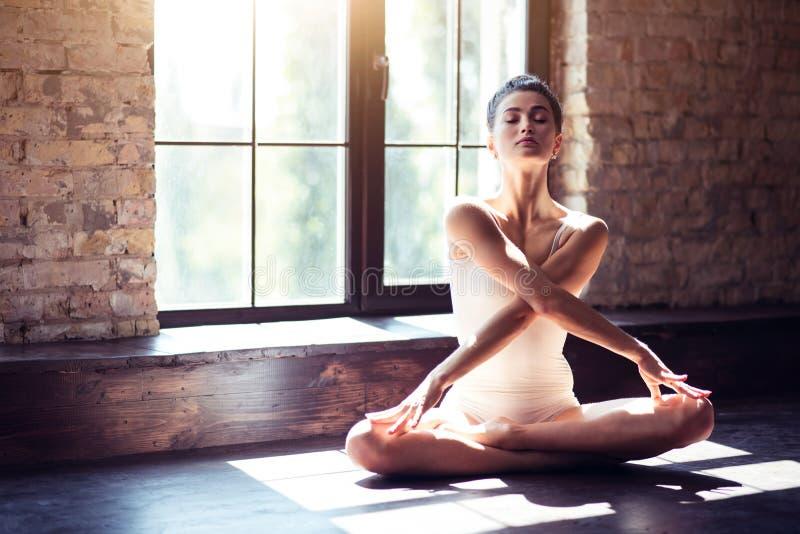 做瑜伽莲花姿势的美丽的女孩 免版税库存照片