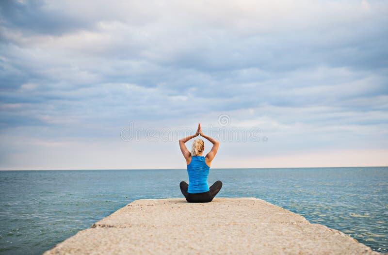 做瑜伽锻炼的一名年轻运动的妇女的背面图由海洋外面 图库摄影