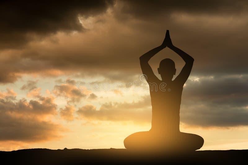 做瑜伽锻炼的女孩在日落 库存图片