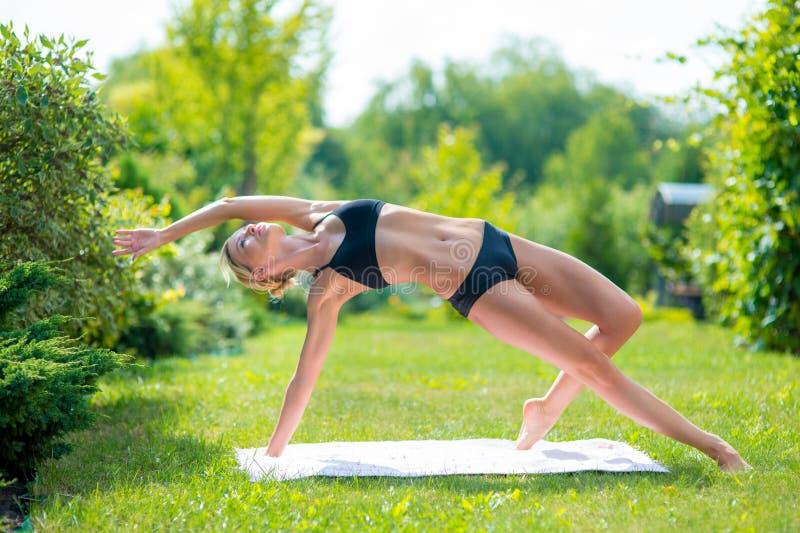 做瑜伽锻炼的少妇在绿草的早晨 免版税库存图片