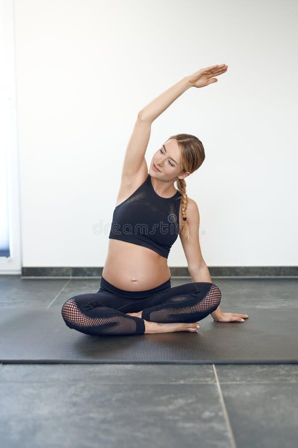做瑜伽锻炼的怀孕的年轻女人 免版税库存照片
