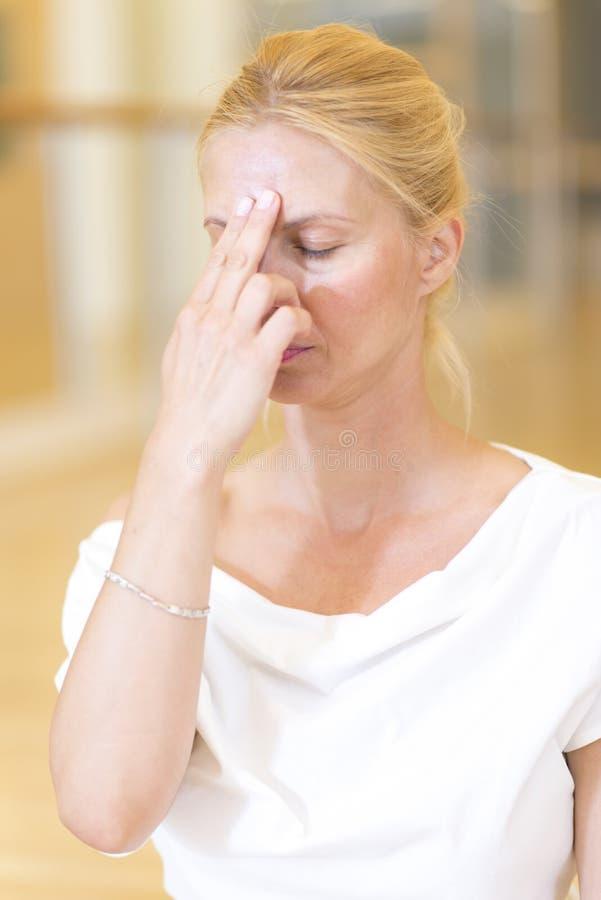做瑜伽锻炼的镇静俏丽的妇女在演播室 免版税库存图片