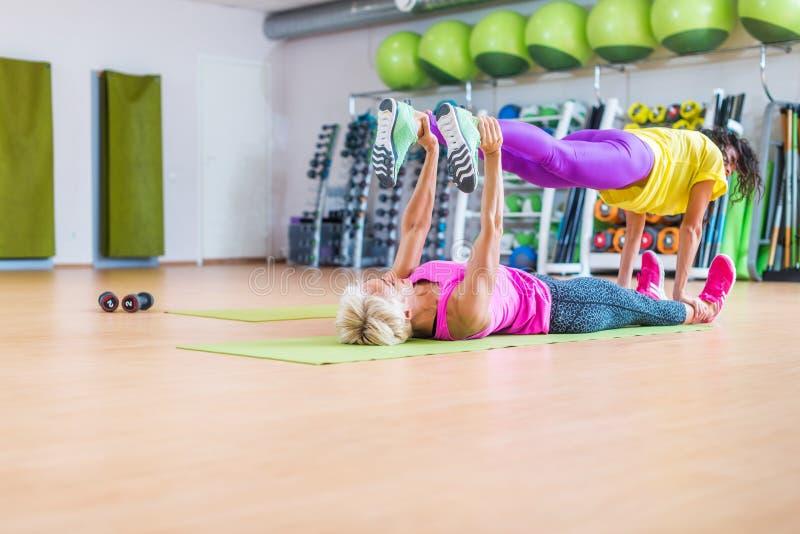 做瑜伽锻炼,一的两个女性健身模型说谎在握别的腿的地板席子在她上在体育 库存照片