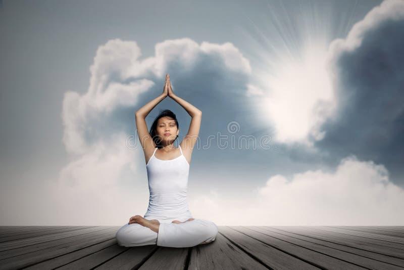 做瑜伽锻炼的亚裔妇女在蓝天下 图库摄影