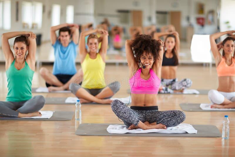 做瑜伽锻炼的年轻女性辅导员 免版税库存图片