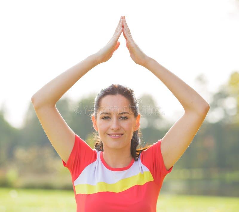做瑜伽锻炼的年轻深色的妇女 图库摄影
