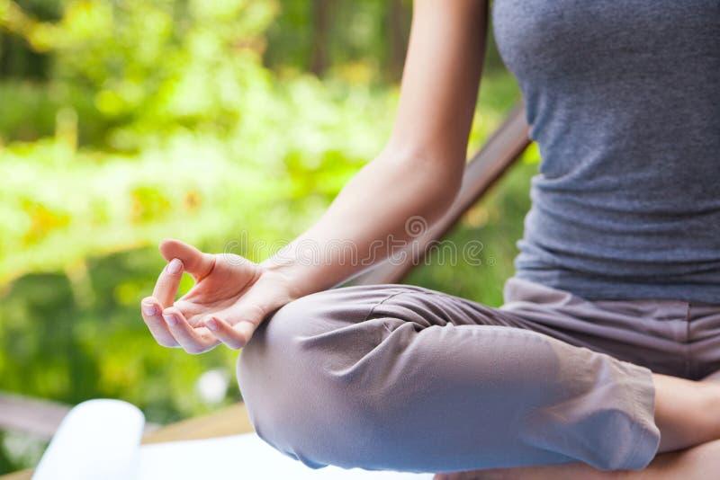 做瑜伽(莲花姿势)的女孩在公园 免版税库存照片