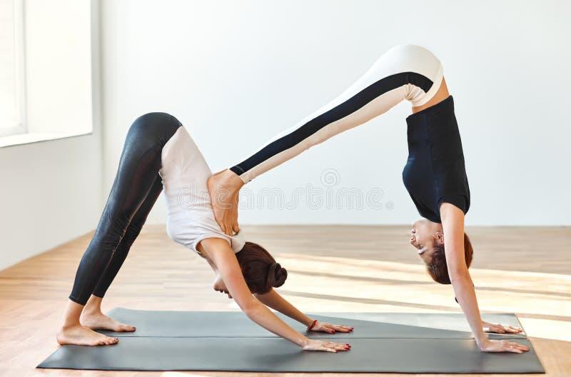 做瑜伽asana双向下狗的两个少妇 图库摄影