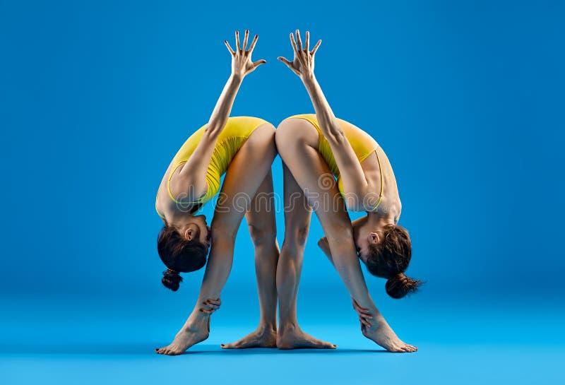 做瑜伽asana的两个少妇站立Parsvottanasana 库存照片