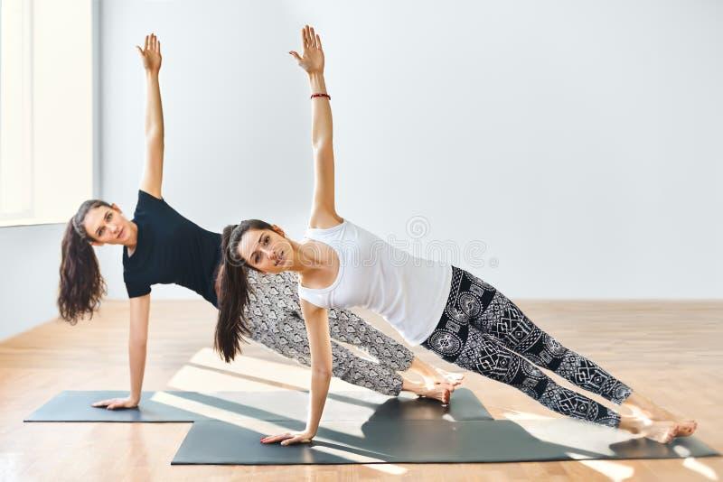 做瑜伽asana边板条的两个少妇 库存照片