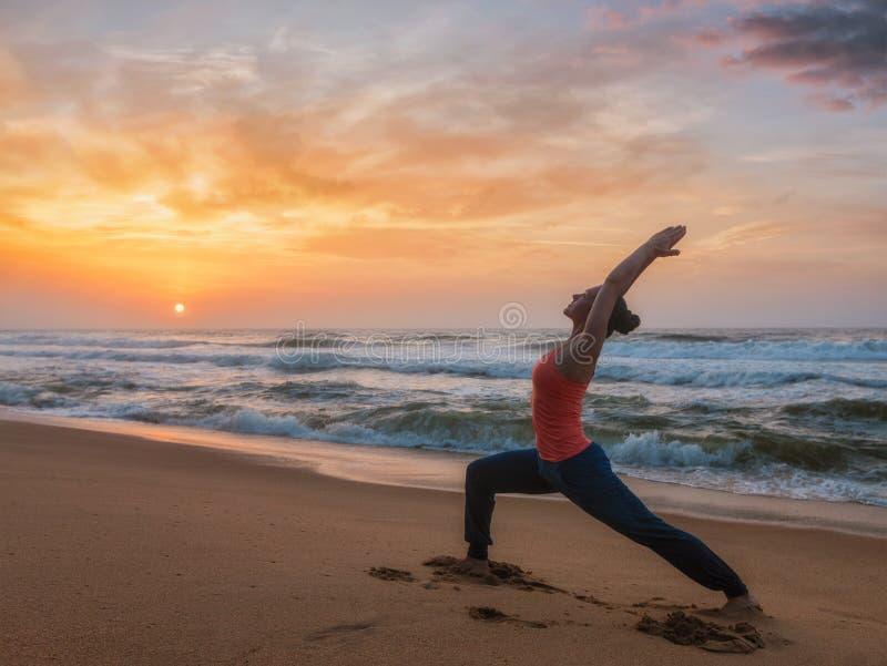 做瑜伽asana virabhadrasana的妇女在海滩的1个战士姿势. 海洋, 培训.
