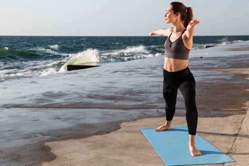 做瑜伽e的美丽的年轻体育妇女全长画象  免版税库存图片