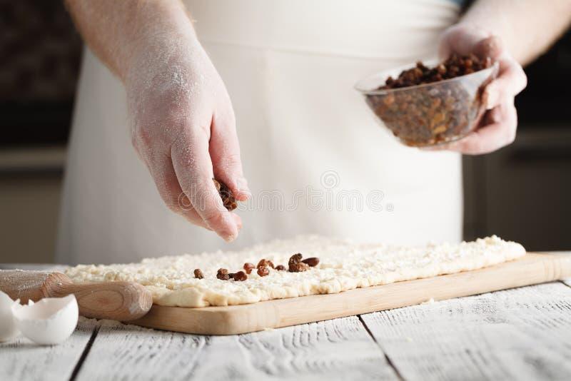 做甜葡萄干面团,拂去面团球的灰尘用面粉的手 库存照片