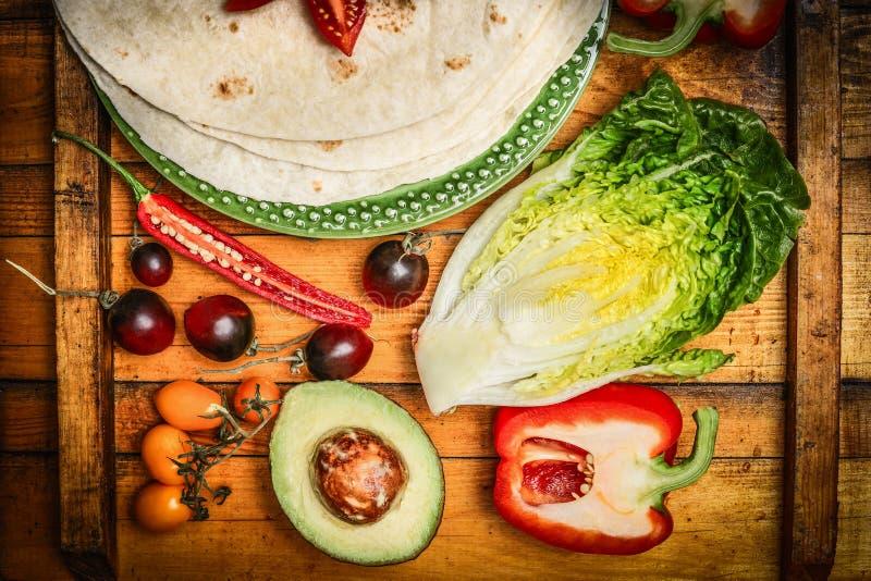 做用新鲜蔬菜的炸玉米饼或面卷饼在土气木背景,顶视图 图库摄影