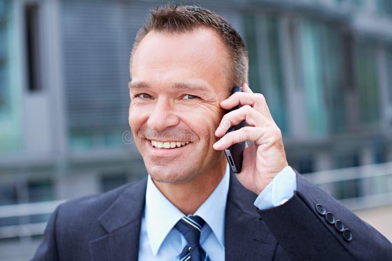 做电话的愉快的商人 免版税库存照片