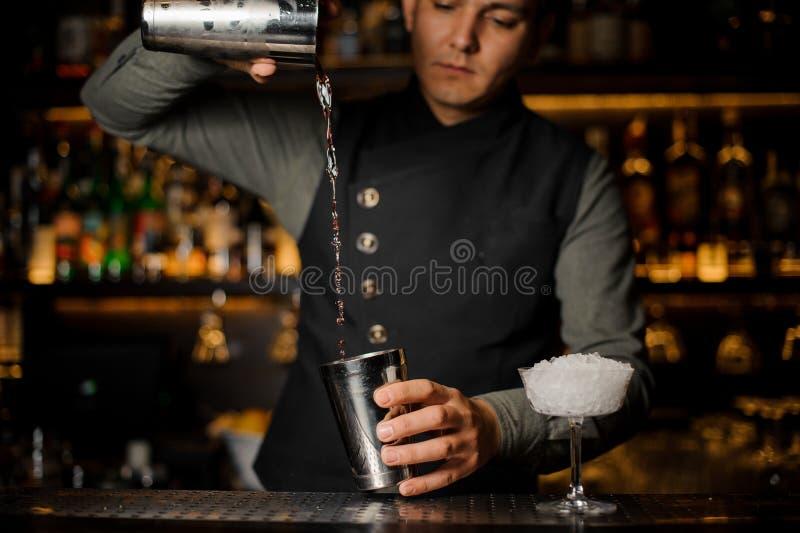 做的一个鸡尾酒男服务员混合的饮料用堪蓓莉开胃酒 免版税库存图片