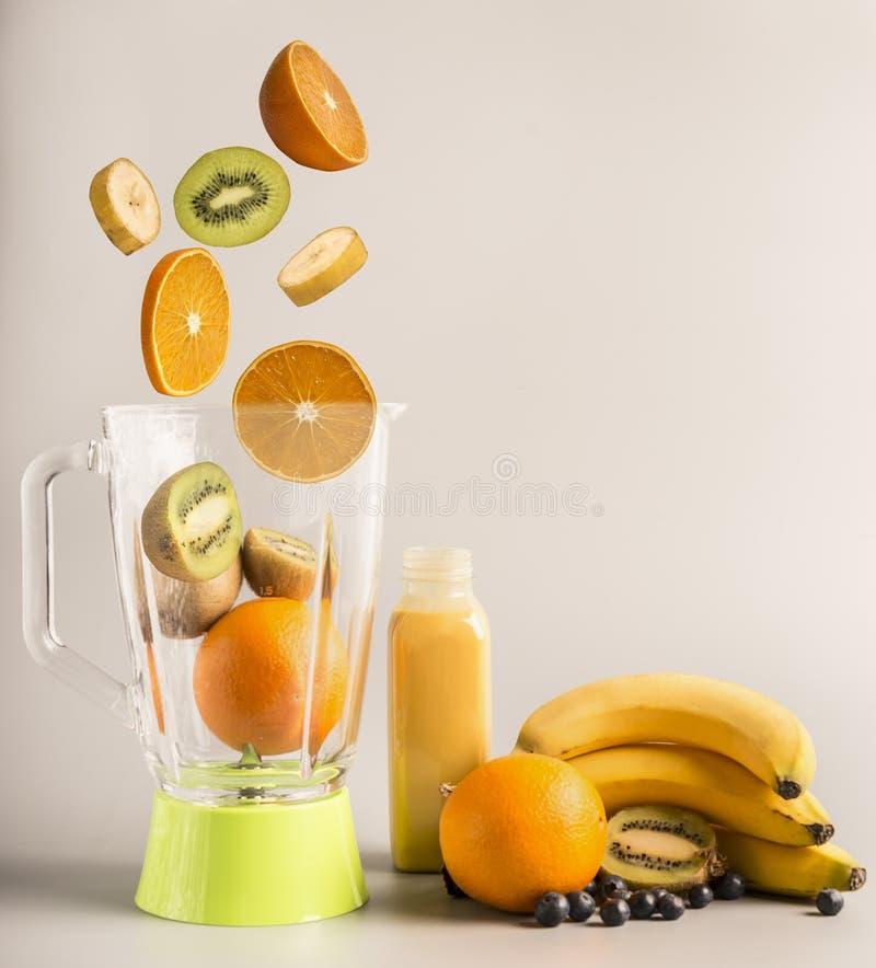 做的圆滑的人飞行成份由桔子、猕猴桃和香蕉,素食健康食物,果子在一块绿色闪光矿物附近排行了 库存图片
