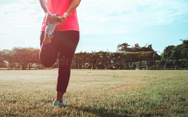 做的妇女舒展腿的锻炼 运动员妇女为跑做准备 低部分视图适合年轻女人舒展 免版税图库摄影