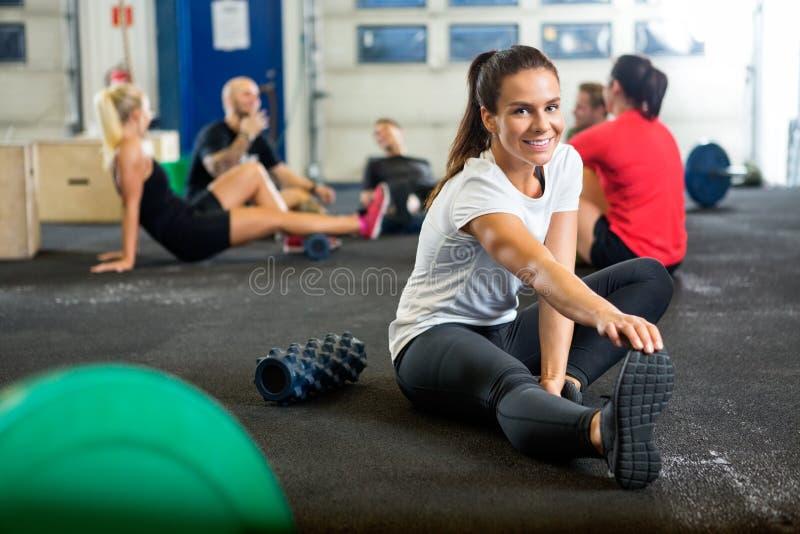 做的妇女舒展锻炼在交叉训练 免版税库存照片