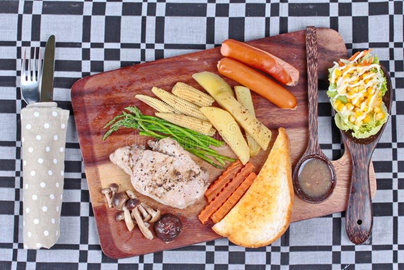 做的家,猪肉牛排和被混合的菜在屠户担当了服务与配菜帕尔马干酪面包,香肠,椎茸fre 免版税图库摄影