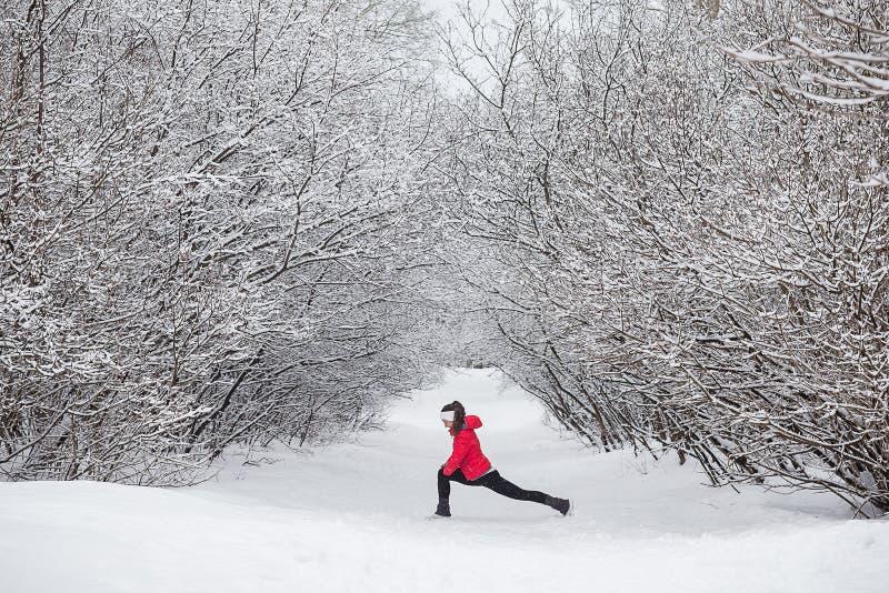 做的少妇舒展锻炼在冬天期间 免版税库存图片