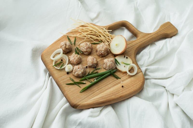 做的汤成份用丸子 生肉、葱和面条在一个木板 库存图片